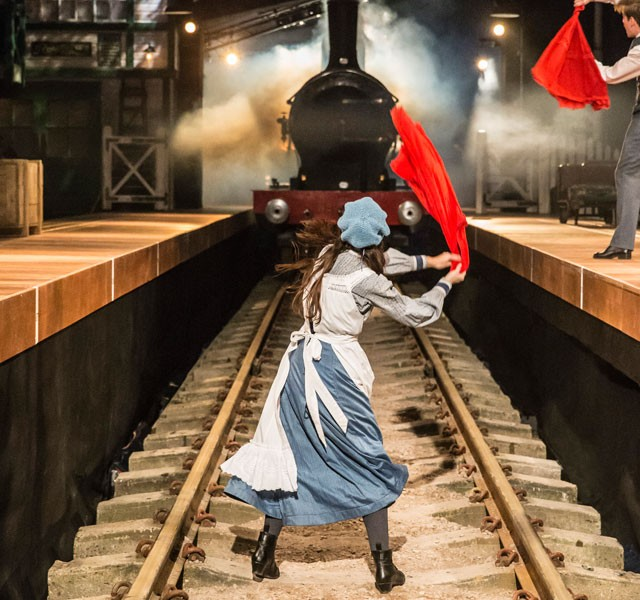 A young girl waving a red sash to warn an oncoming train